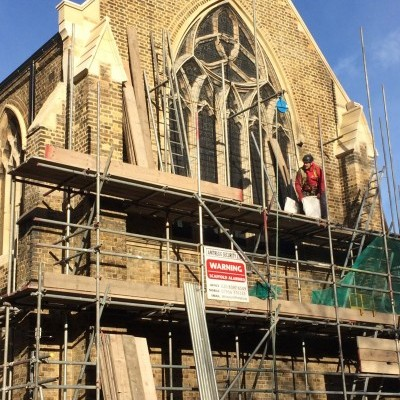 Removal of scaffolding from east end shows new stonework and window guard